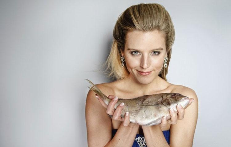 Devojka drži ribu u rukama