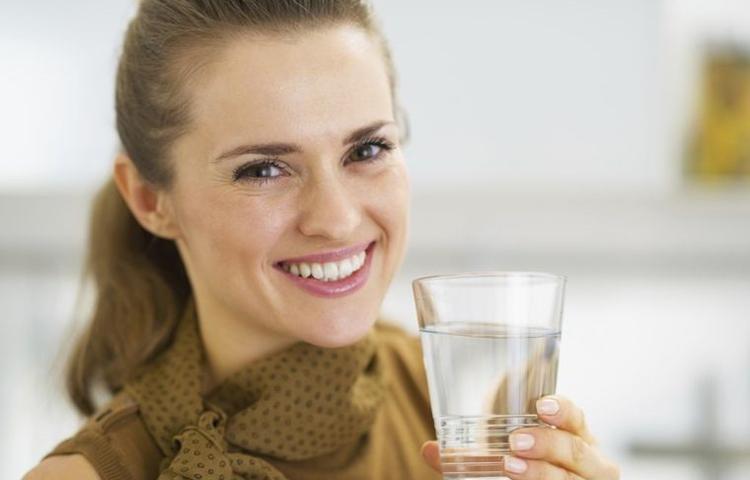 Devojka drži čašu u ruci
